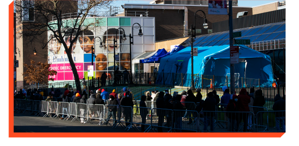 Large line of people standing outside a medical tent