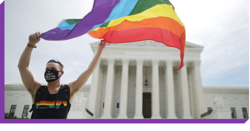 Person waving a Pride flag in front of the Supreme Court building