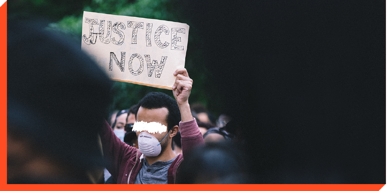 Protester holding sign that says ''Justice Now''