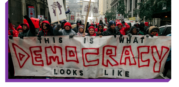 Chicago teachers holding a sign that says ''This Is What Democracy Looks Like''