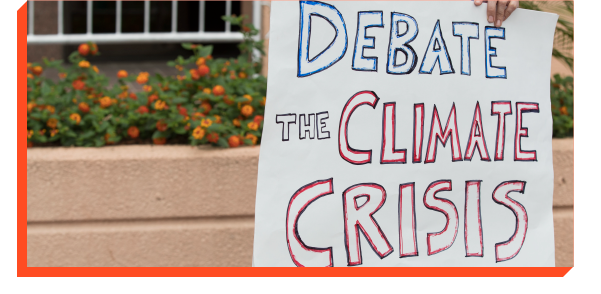 Protester holding sign that says ''Debate The Climate Crisis''